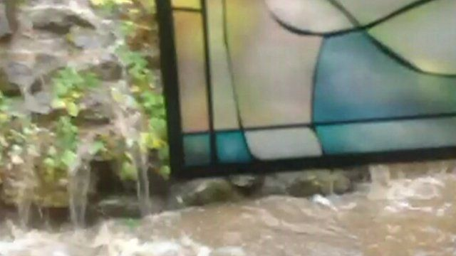 Stain-glass window surrounded by flood waters