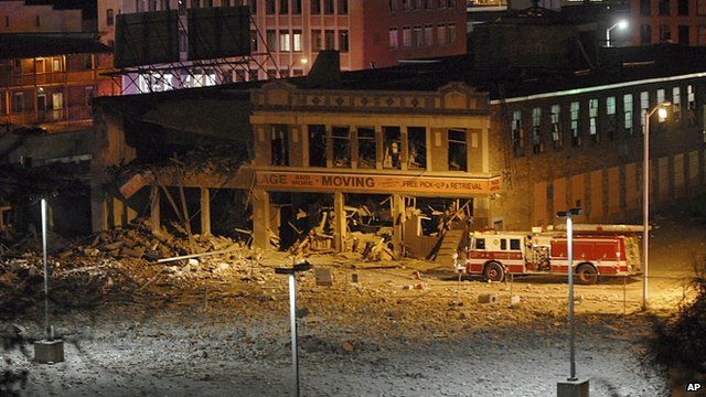 A fire truck is parked next to a damaged building after a nearby gas explosion levelled another building in Springfield