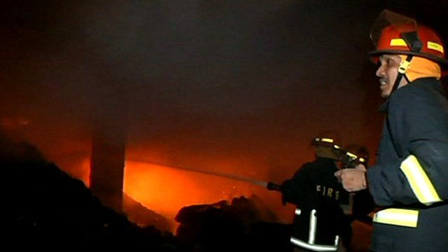 Firefighter tries to dampen the flames of the fire outside Dhaka