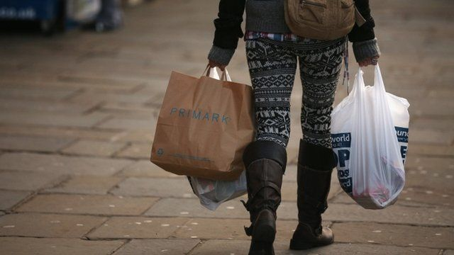 A woman carries several shopping bags from discount shops