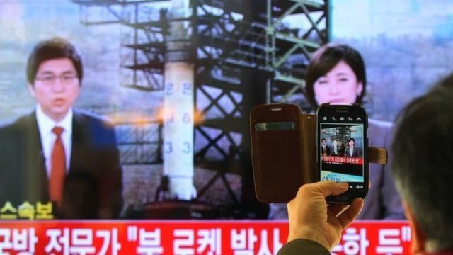 South Korean man in front of a television screen reporting the rocket news at Seoul Railway Station in South Korea on 12 December 2012