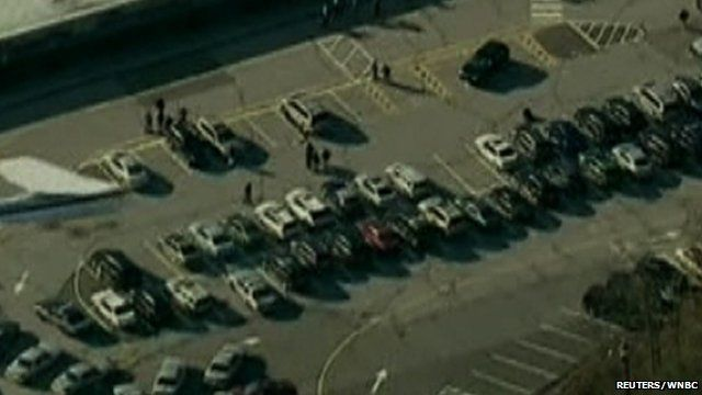 Police and emergency personnel set up in the parking lot after a shooting at Sandy Hook Elementary School in Newtown, Connecticut.