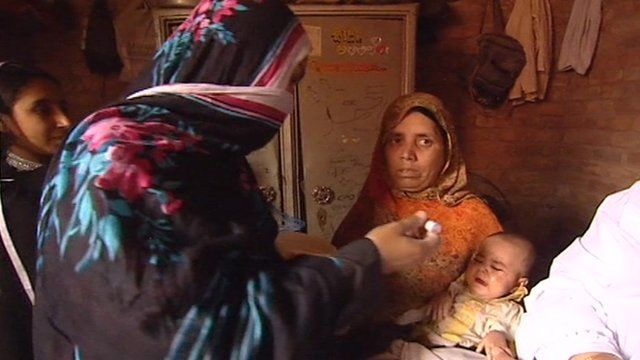 Woman giving baby polio vaccination