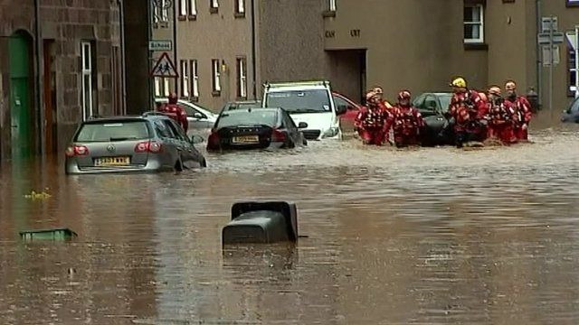 Rescue teams dragging inflatable down flooded street