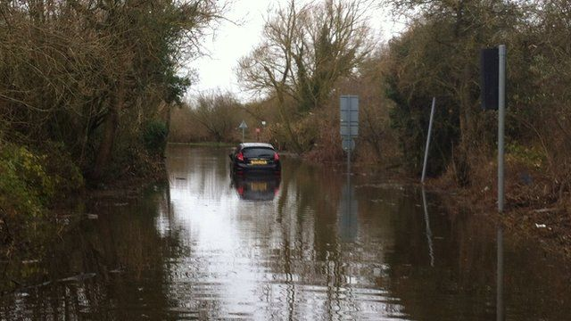A stranded car in Pingewood where Berkshire Fire and Rescue are working to pump water away from an electricity distribution centre