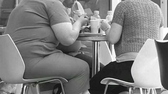 Obese people eating at table
