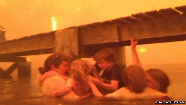 The Holmes family take refuge from the flames under a jetty