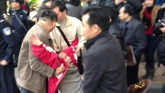 Protester carried by three men