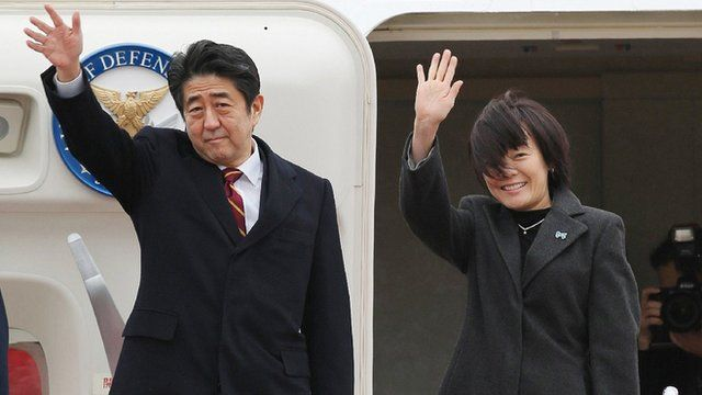 Japanese Prime Minister Shinzo Abe and his wife Akie, wave as they leave Tokyo International Airport on January 16, 2013, en route to Hanoi