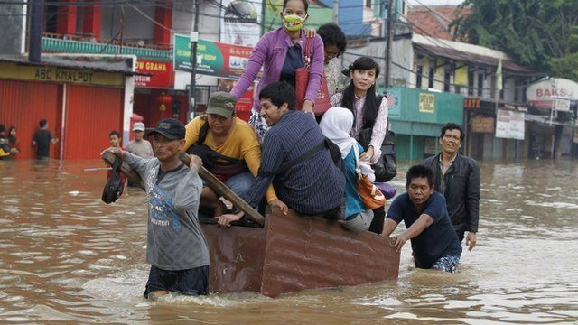 People being transported across a flooded road on a wooden cart in Jakarta