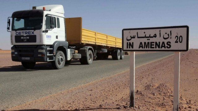 Truck passing by a sign for In Amenas