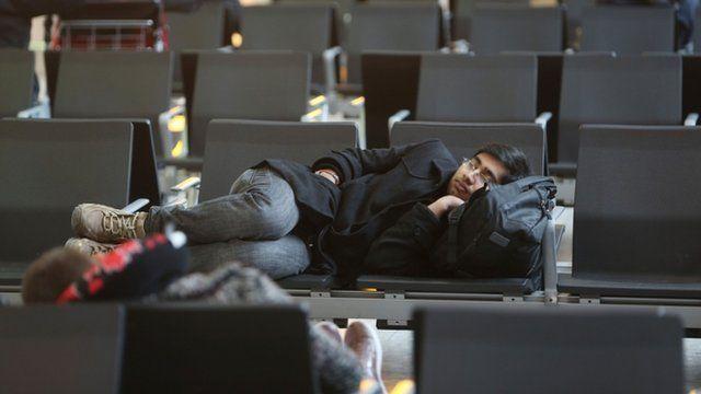 A man asleep on chairs at Terminal 5