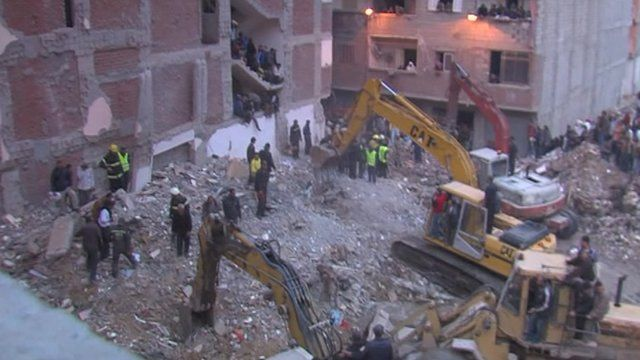 Diggers and emergency workers at site of collapsed building