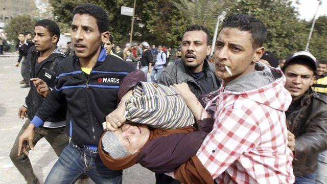 """Demonstrators against Egypt""""s President Mursi help a fellow protester"""