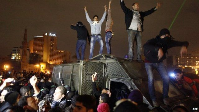 Protesters climb on top of a police vehicle in Tahrir Square, Cairo (28 January 2013)
