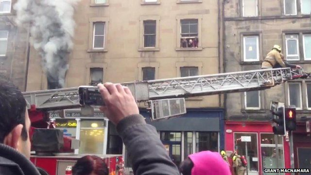 Firefighters rescue a woman from a fire