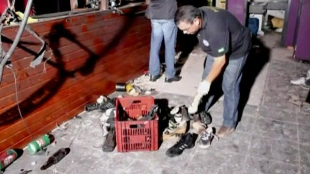 Officials sifting through the belongings those who were in the Kiss nightclub, Brazil