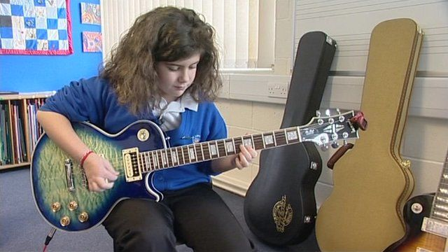 Ayla playing the guitar.