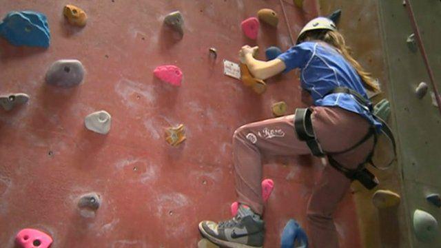 School pupil climbing a climbing wall