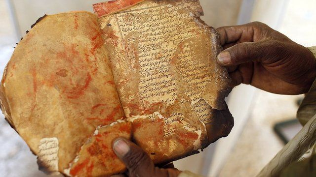 A museum guard displays a burnt ancient manuscript at the Ahmed Baba Institute in Timbuktu on 31 January 2013