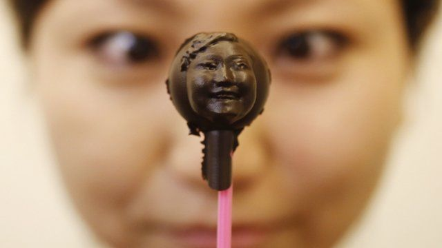 Woman holding a chocolate sculpture of her face