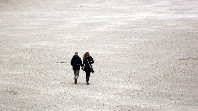 A couple walk on the beach