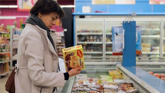 Woman looks at beef product in supermarket