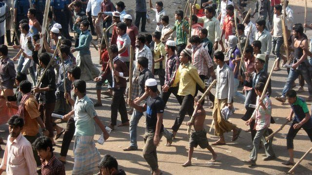 Jamaat-e-Islami activists march with sticks and set fires in the street during a clash with police in Chittagong