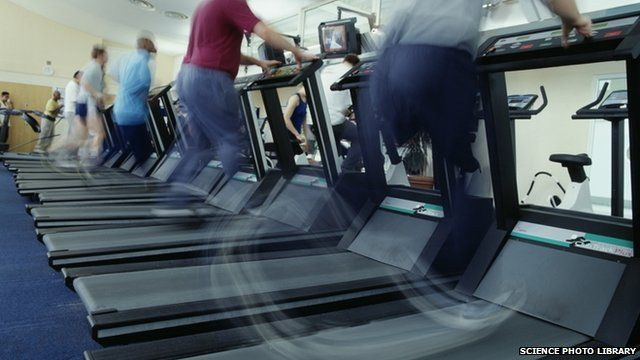 Men in a gym exercising on running machines