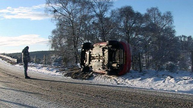 Man stands by an overturned car