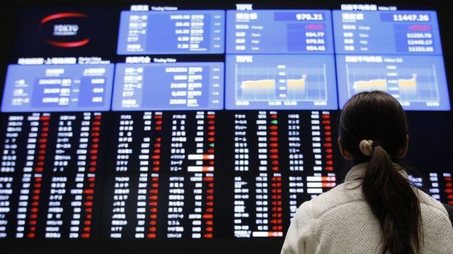 A woman looks at an electronic board showing Japan's stock price index at the Tokyo Stock Exchange