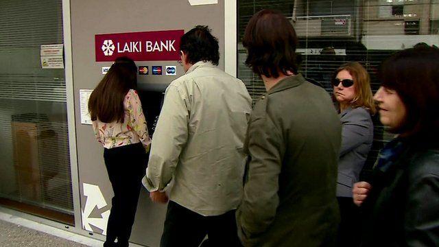 Bank customers queue at ATM in Nicosia
