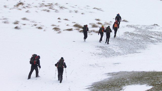 Rescue workers cross a snowscape