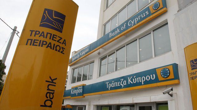 A Bank of Cyprus branch with a Piraeus Bank logo seen in foreground, in Athens
