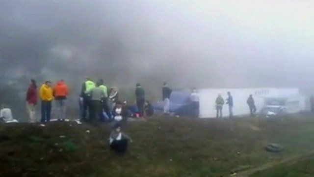 People standing on grass verge at accident scene