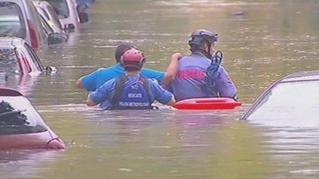 Rescuers wade through water