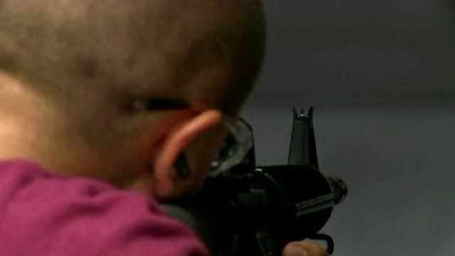 Man aims rifle