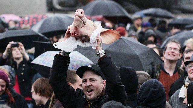 Man holds pig head aloft