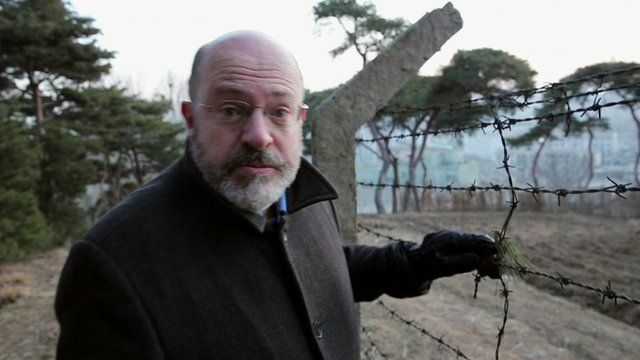 John Sweeney next to barbed wire fence