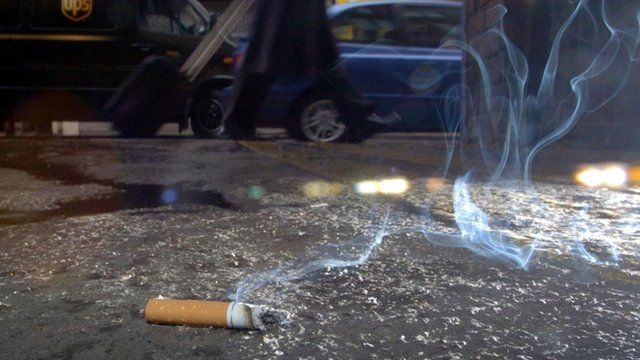 Cigarette left smoking on a pavement