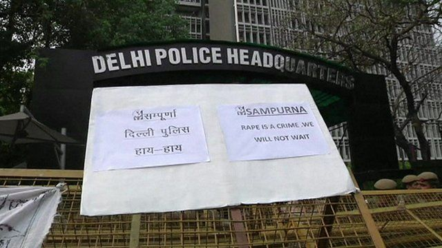 Delhi police headquarters with protesters' placard