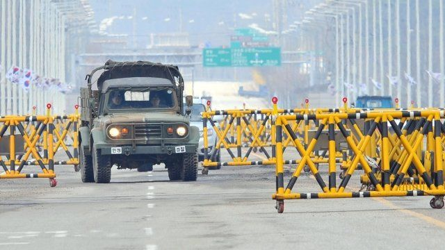 "A South Korean military vehicle drives past barricades on the road leading to North Korea""s Kaesong industrial complex,"