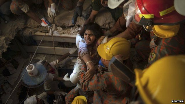 Rescue workers release a garment worker from the rubble of the collapsed Rana Plaza building