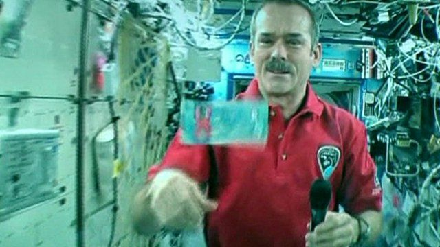 Astronaut Chris Hadfield with the new note floating in space