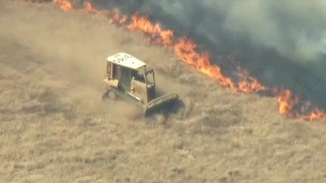 A vehicle drives along a field next to a line of wildfire