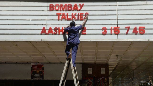 """An employee of the New Excelsior Theatre puts up letters spelling out the movie """"Bombay Talkies"""" in Mumbai"""