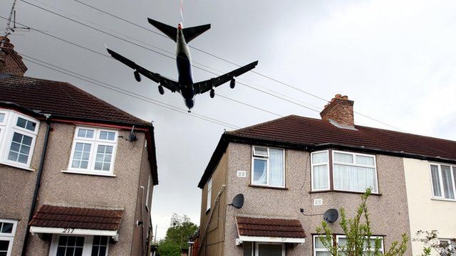 Plane flying over a housing estate outside Heathrow Airport