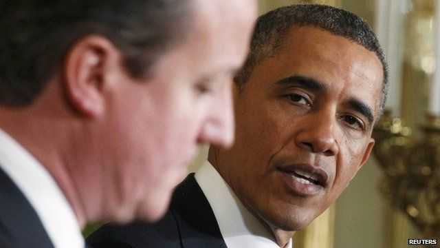 """U.S. President Barack Obama (R) looks toward Britain""""s Prime Minister David Cameron (L) during a joint news conference in the East Room of the White House in Washington"""