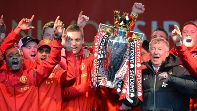 Retiring iconic Manchester United manager Alex Ferguson (R) and his players hold the Premier League trophy outside the town hall in Manchester