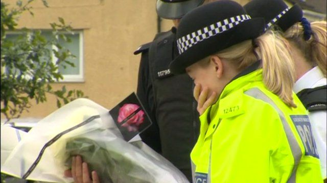 A police officer visits the memorial of PCs Fiona Bone and Nicola Hughes